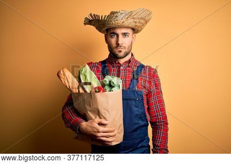 Young rural farmer man holding fresh groceries from marketplace over yellow background with a confident expression on smart face thinking serious