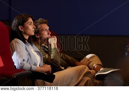 Side View Portrait Of Young Couple In Cinema Watching Movie While Sitting On Red Velvet Chairs In Da