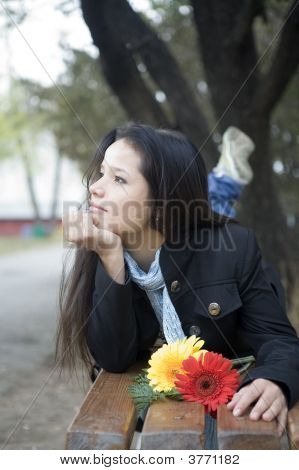 Girl With Flowers Laying On The Bench In Autumn Park