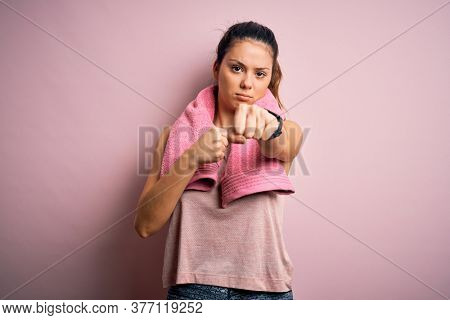Young beautiful brunette sportswoman wearing sportswear and towel over pink background Punching fist to fight, aggressive and angry attack, threat and violence