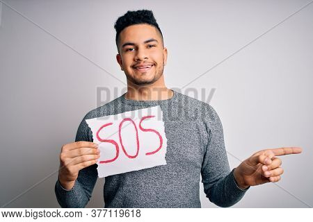 Young handsome man with problem holding banner with sos message over white background very happy pointing with hand and finger to the side