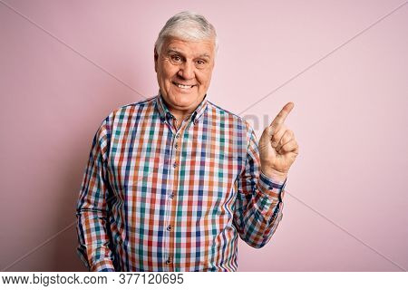 Senior handsome hoary man wearing casual colorful shirt over isolated pink background with a big smile on face, pointing with hand finger to the side looking at the camera.