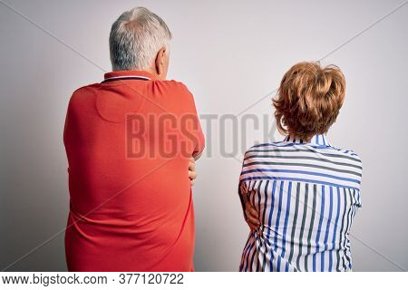 Senior beautiful couple standing together over isolated white background Hugging oneself happy and positive from backwards. Self love and self care