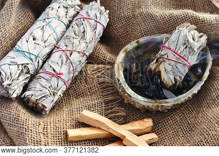 An Image Of White Sage Smudge Sticks An Abalone Shell On Beige Sackcloth.