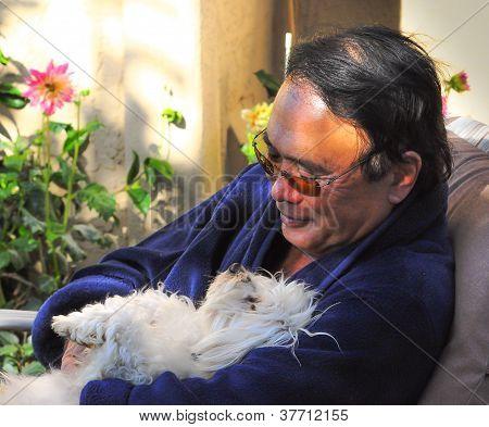 senior man holding pet dog