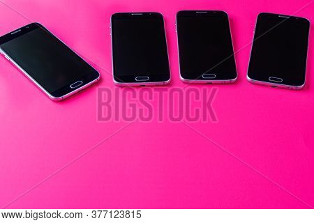 Several Smartphones Lying On A Pink Background Angle View Modern Technology Mobile Communications.
