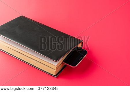 Smartphone Is Used As Bookmark In The Book On Pink Background.