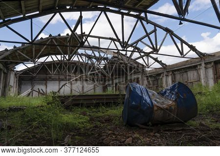 An Old Abandoned Warehouse Hangar With A Ruined Leaky Roof And Wooden Floors, Overgrown With Grass I