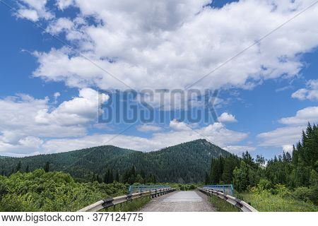 A Road In A Hilly Area And A Cloudy Blue Sky, Mountains In The Background. Picturesque Landscape Of