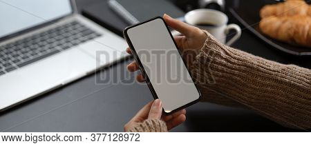 Female Take A Break With Mock Up Smartphone While Sitting At Workspace With Laptop, Coffee And Crois