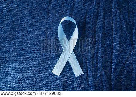 Prostate Cancer Awareness, Light Blue Ribbon On Male Jeans Background. Closeup, Hope, Cure, Treatmen