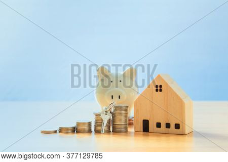 Key Placed Front Of Stack Coins With Model House And Piggy Bank. Mortgage And Real Estate Investment