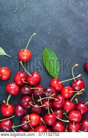 Pile Of Cherry With Leaf And Water Drops On Black Stone Table. Ripe Ripe Cherries. Sweet Red Cherrie