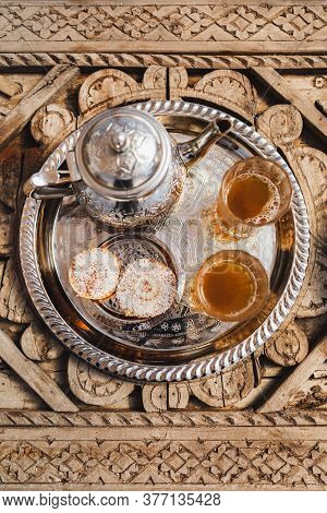 Traditional Moroccan Mint Tea With Cookies On Silver Tray On Carved Wooden Table. Beautiful Vintage