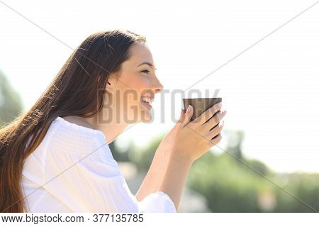Side View Of A Happy Woman Holding A Coffee Cup Looking Away Outdoors Contemplating Views
