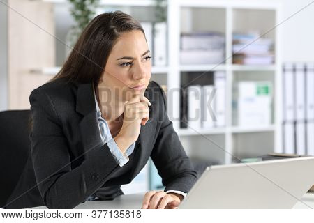 Pensive Executive Woman Thinking Looking Awaywith Laptop Sitting On Her Desk In The Office