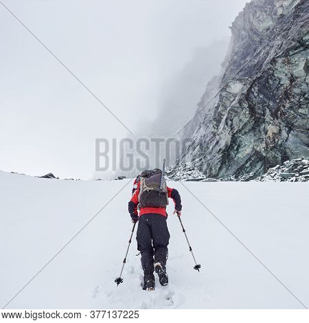 Back View Of Male Traveler With Backpack Walking Through The Snow In Winter Mountains. Backpacker Wi