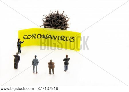 Meeting With Miniature Figurines Posed As Business People Standing Around Post-it Note With Coronavi