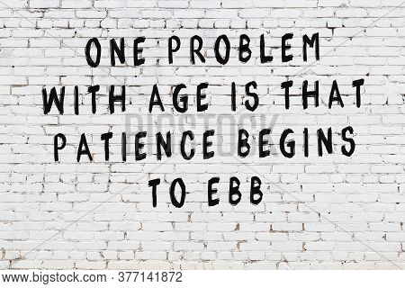 White Brick Wall With Black Painted Inscription Of Sensible Wise Quote On It