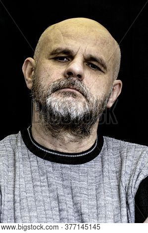Portrait Of A Bald Man With A Gray Beard On The Black Background