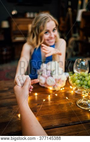 Female Hand With A Wedding Ring In The Foreground. A Marriage Proposal On A Romantic Dinner.