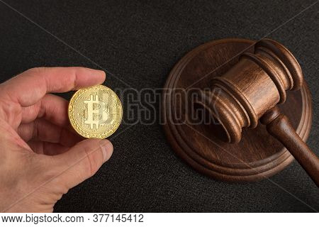 Law Or Auction Gavel And Bitcoins In Hand. Dispute Resolution On Bitcoin Frauds. Cryptocurrency Legi