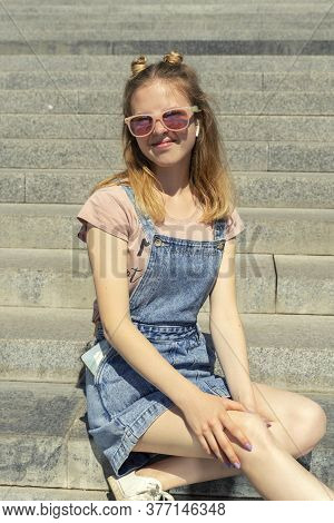 Beautiful Young Red-haired Girl In Sunglasses Sits On The Stone Steps And Sincerely Smiles
