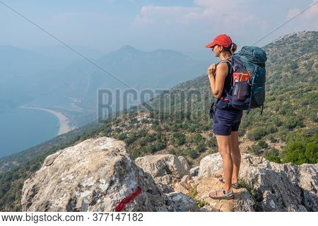 Young woman with backpack enjoy the view of Blue Lagoon in Oludeniz from the beginning of the Lycian Way trail in Turkey. Lycian way hiking trail at Mediterranean coast in Turkey.