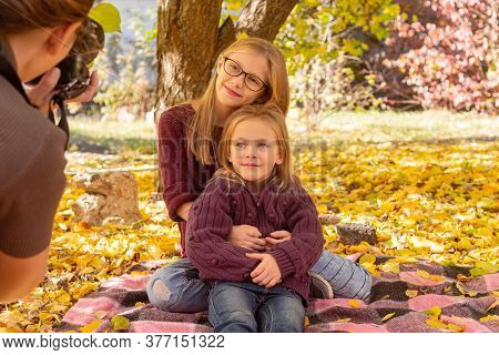 Photographer Woman Photographing Two Children Among The Autumn Leaves