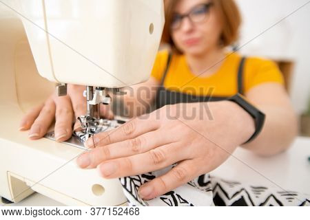 Hands of young contemporary seamstress sitting by electric sewing machine while working over new piece of cloth at home