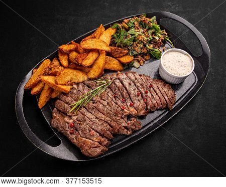 Sliced Grilled Beef Steak Served With Fried Potatoes, Pepper Sauce And Green Leaf Lettuce