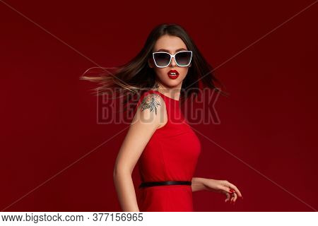 Portrait Of Luxurious Chic Brunette Woman With Flying Hair In White Sunglasses On Red Background