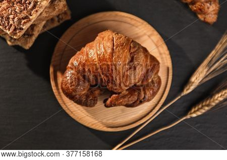 A Croissant On A Round Wooden Cutting Board Accompanied By 2 Ears Of Wheat, Other Pasta And Croissan