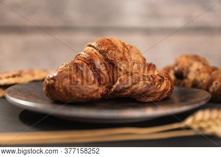 A Croissant On Top Of A Plate Of Dark Mottled Ceramic, Accompanied By 2 Ears Of Wheat, Other Pasta A