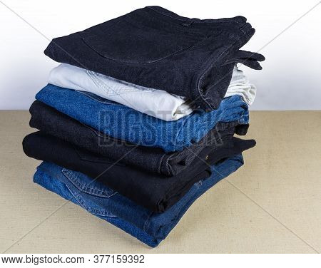 Different Pairs Of Jeans Various Colors And Textures Folded In The Stack