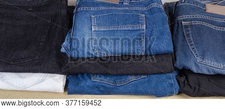 Folded Different Pairs Of Jeans Various Colors And Textures, Fragment Close-up, Background