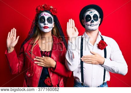 Couple wearing day of the dead costume over red swearing with hand on chest and open palm, making a loyalty promise oath