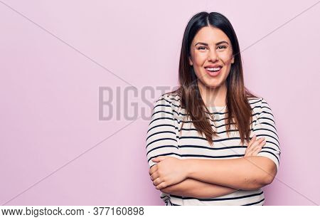 Young beautiful brunette woman wearing casual striped t-shirt over isolated pink background happy face smiling with crossed arms looking at the camera. Positive person.