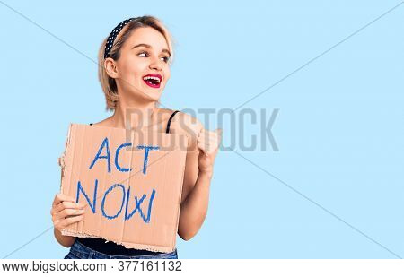 Young beautiful blonde  holding act now banner pointing thumb up to the side smiling happy with open mouth