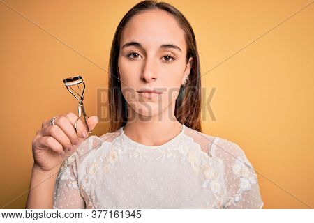 Young beautiful woman using eyelash curler standing over isolated yellow background with a confident expression on smart face thinking serious