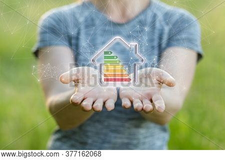 Energy Efficient Home Concept. A Woman Shows A Model Of An Energy-saving House.