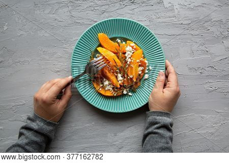 Healthy Pumpkin Seasonal Salad With Cheese On Grey Concrete Background, Top View. Female Hands Hold