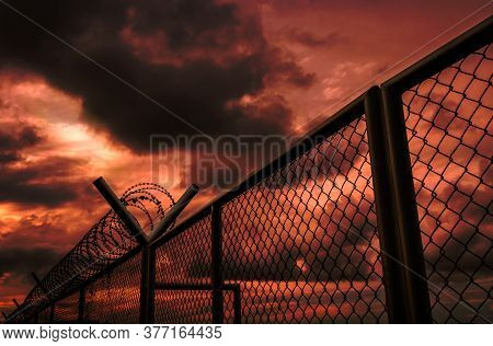 Security Fence Of Military Zone Or Private Area Fence With Red Sky And Dark Clouds. Barbed Wire Secu