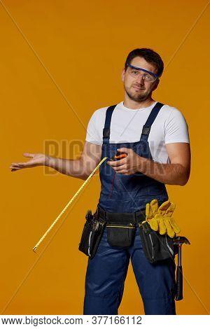 Confused Caucasian Repairman Worker In Uniform Holding Measure Tape And Shrugging Shoulders. Handyma