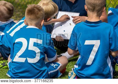 Group Of Young Boys In Blue Shirts Sitting On Sports Grass Field Witch School Coach. Kids Listening