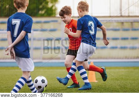 Youth Junior Athletes In Red And Blue Soccer Shirts. Sports Education. Kids Football Players Kicking
