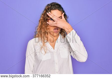 Young beautiful woman with blue eyes wearing casual shirt and glasses over purple background peeking in shock covering face and eyes with hand, looking through fingers with embarrassed expression.