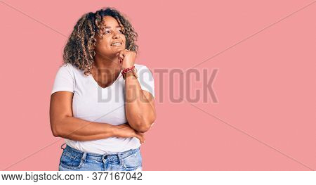 Young african american plus size woman wearing casual clothes with hand on chin thinking about question, pensive expression. smiling with thoughtful face. doubt concept.