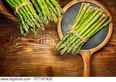 Asparagus. Fresh raw organic green Asparagus sprouts closeup. On wooden table background. Healthy vegetarian food. Raw vegetables, market. Healthy eating concept, diet, dieting. Top view, flat lay.