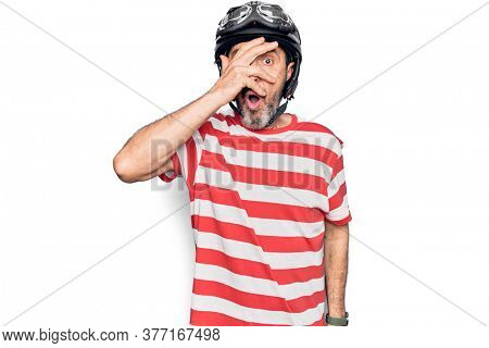 Middle age handsome motorcyclist man wearing moto helmet over isolated white background peeking in shock covering face and eyes with hand, looking through fingers afraid